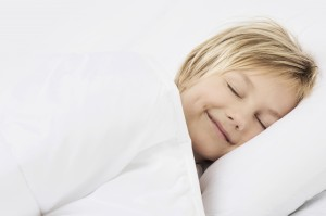 Boy sleeping in bed and smiling